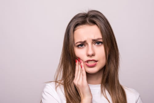 Woman grimacing while holding her hand against her jaw
