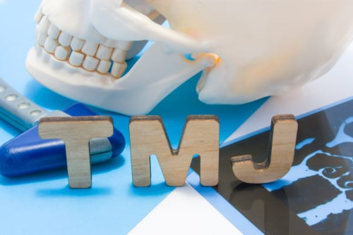 Scull and jawbone sitting on the initials TMJ