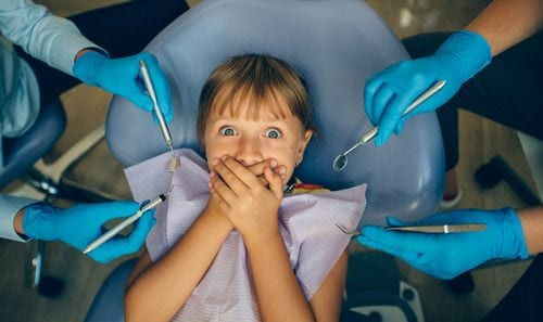 A child with a cavity is afraid of the dentist because of what her parents have said.