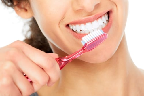 A woman maintaining a 45-degree toothbrush angle as she brushes her teeth for a minimum of two minutes