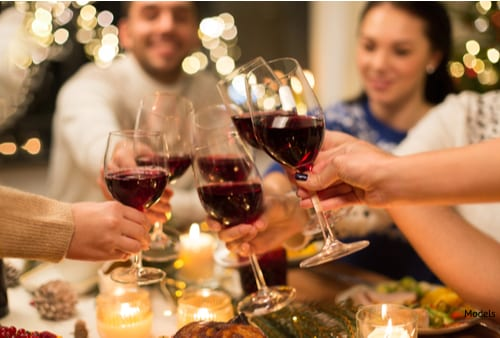 Many alcoholic drinks enjoyed during the holiday season, like the group pictured above drinking red wine, are high in sugars that can eventually lead to tooth decay and damage.