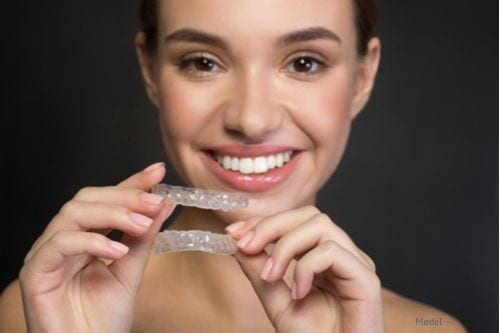 Woman excited about wearing her ClearCorrect™ aligner trays to give her a beautiful smile.
