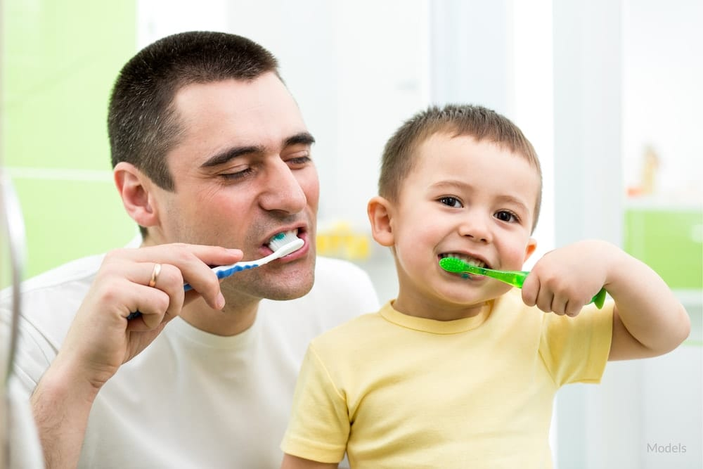 Father showing his son the right way to brush his teeth.