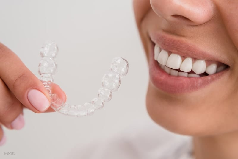 woman beautiful smile holding a transparent brace mold