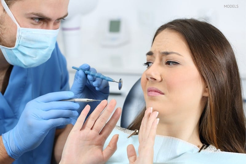 Scared patient sitting in the dental chair while the dentist is trying to examine her.